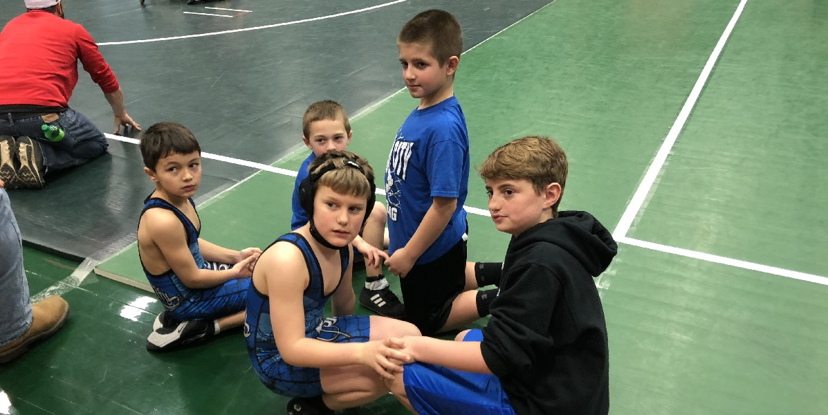 A group of young wrestling competitors crouch together